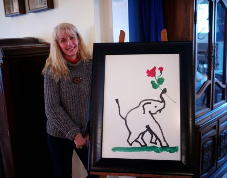 Pegi in her living room with a work of art painted by an elephant. (I kid you not!)  Quirky indeed. By Paul Goldfinger ©