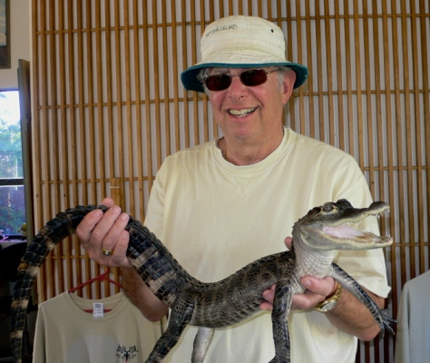 Paul holds an alligator. It feels like a chicken. (That means it wants a chicken).