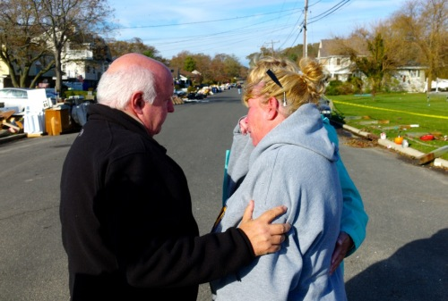 Shark River Hills.  November 1, 2012.  Comitteeman Randy Bishop comforts a resident after scavengers try buy her furniture drying outside.   By Paul Goldfinger