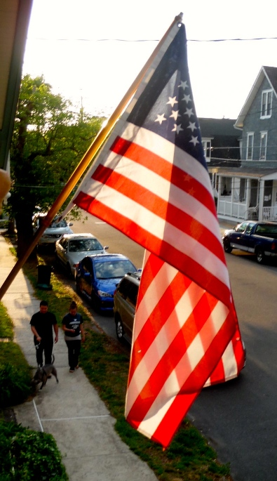 Oh say can you see Jean Bredin catching the light through the flag from her upper porch on Heck Avenue.   Blogfinger staff photograph. ©