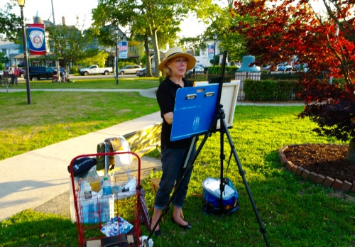 Janet Whritner in Firemen's Park where she is painting the town red, and other colors too. Her subjects are two adjacent Victorian cottages on Mt. Hermon Way. Paul Goldfinger photo © 7/15/16