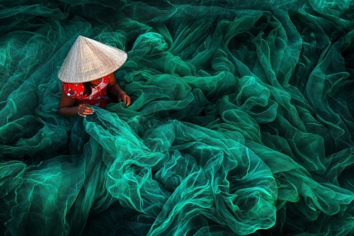 In a village in southern Vietnam, a woman weaves a fishing net. By tradition, Vietnamese women make nets for their husbands. Danny Yen Sin Wong