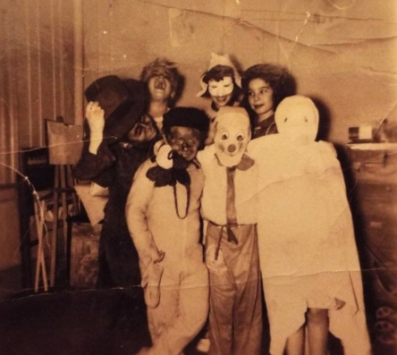 1953. Halloween in Washington Heights was always fun. We never left the building, knocking on everyone's door asking ' Anything for Halloween?' You got a couple of pennies, and if you were lucky, you got a nickel. Nobody gave out candy. This is one of my treasured photographs, I was 12 and I am standing in the back row with the mask. My mother made the costume. I was a Dutch Girl.